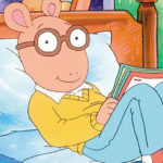 Arthur the cartoon sitting on a bed reading a book