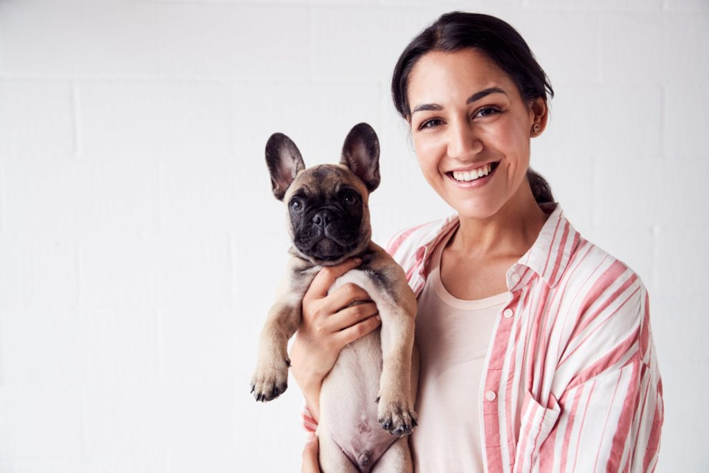 Woman holding her French Bulldog